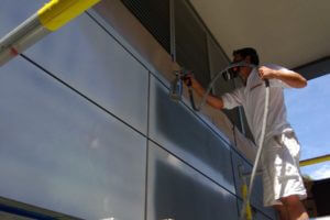 painting technician spraying painting exterior commercial building