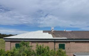 professional painter undertaking asbestos encapsulation building roof