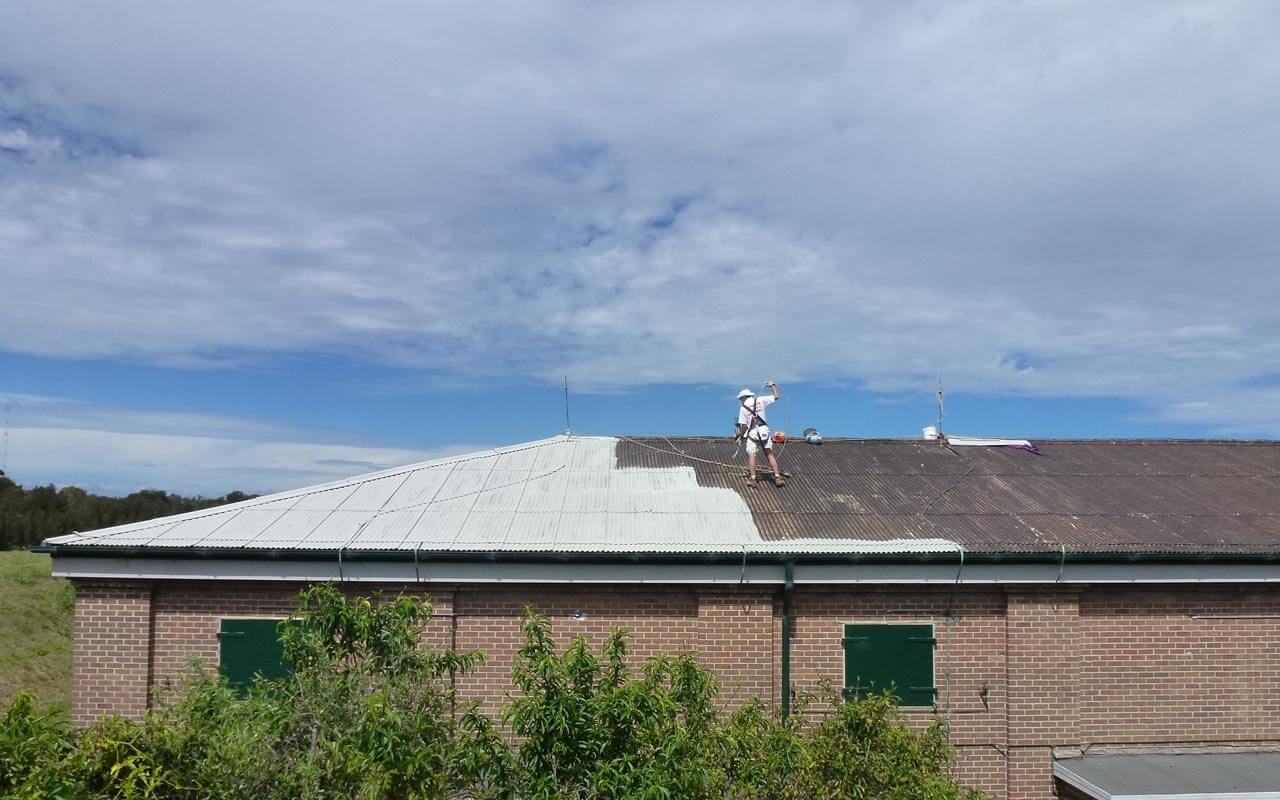 professional painter undertaking asbestos encapsulation building roof